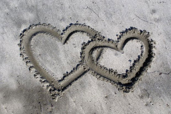 linking hearts in sand